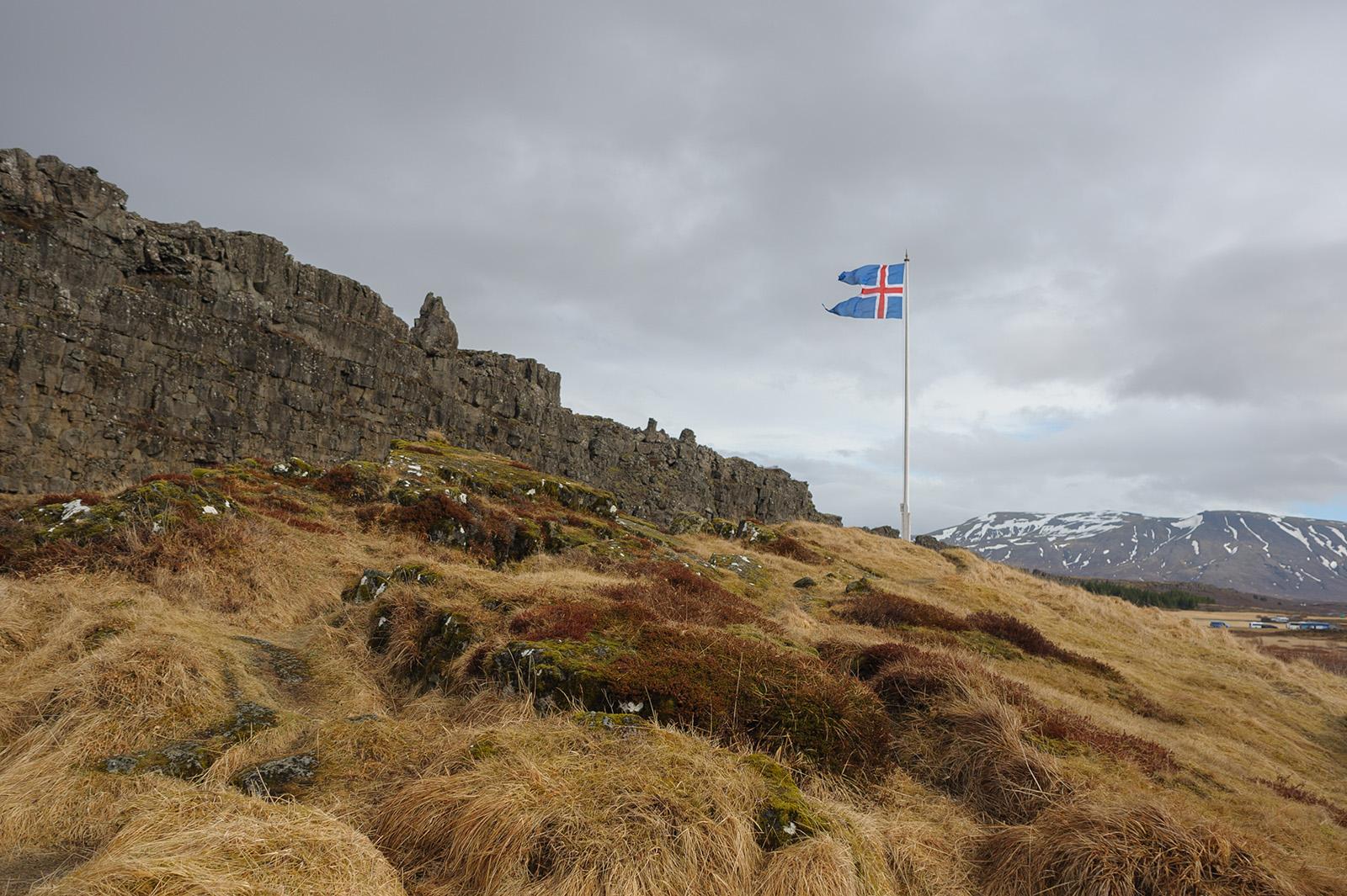 Þingvellir. Цвета флага связывают с исландским пейзажем: красный цвет — цвет огня исландских вулканов, белый — цвет льдов и снегов, а синий — цвет вод Атлантического океана, окружающего остров.